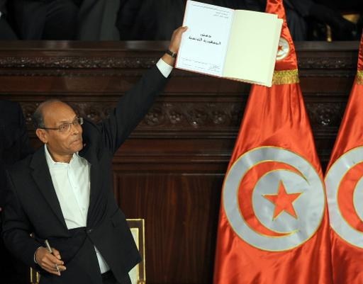 Tunisian president Moncef Marzouki shows a copy of the new constitution after its adoption on January 27, 2014 in Tunis  (AFP, Fethi Belaid)