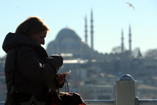 A Turkish woman looks at her smartphone in the Eminonu district of Istanbul, with the Suleymaniye mosque in the background, on March 21, 2014  (AFP, Ozan Kose)
