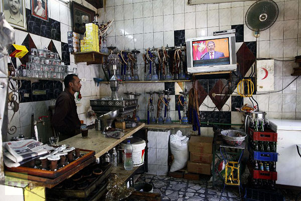 An Egyptian man working at a traditional coffee shop watches Morsi taking his oath.  (AFP Photo/Mahamud Khaled)