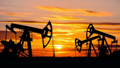 Industrial landscape. US Oil Field. Oil pumps against the setting sun. Daily News Egypt