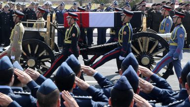 Officers salute as the horse-drawn carriage transporting the flag-draped coffin former Egyptian President Hosni Mubarak passes by during the funeral at Mosheer Tantawy mosque