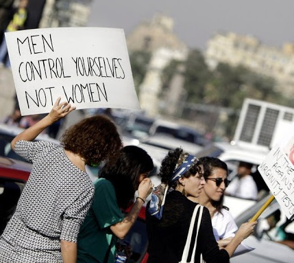 Female protester against sexual abuse carrying a sign saying men control yourselves not women