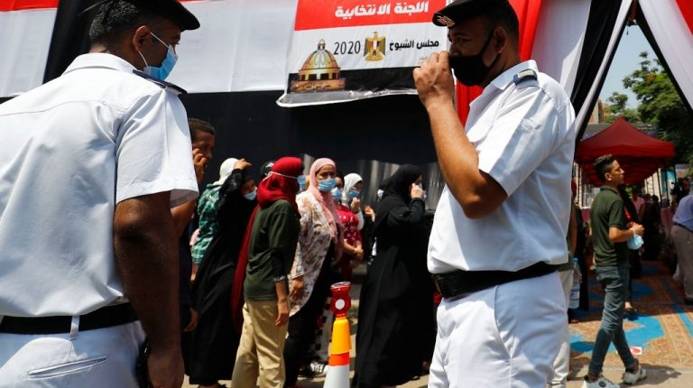 Egyptians, mask-clad due to the COVID-19 coronavirus pandemic, queue up outside a polling station on August 11, 2020 for a new senate in an upper house election. - The two-day vote for 200 of the Senate's 300 seats will be largely contested by candidates who back President Abdel Fattah al-Sisi, who has quietened most opposition within and outside the legislature. (Photo by Khaled DESOUKI / AFP) (Photo by KHALED DESOUKI/AFP via Getty Images)