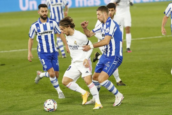 Alaves' Florian Lejeune (R) vies with Real Madrid Luka Modric (C) during a Spanish football league match between Real Madrid and Deportivo Alaves in Madrid, Spain, Nov. 28, 2020. (Photo by Edward F. Peters/Xinhua)