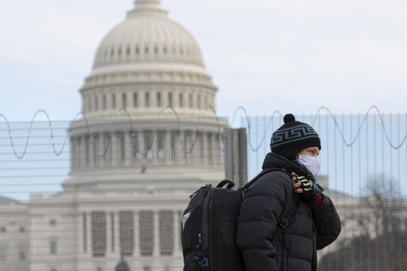 A man wearing a face mask walks past the U.S. Capitol building in Washington, D.C., the United States, Jan. 24, 2021. Amid surge in US COVID-19 cases (Photo by Aaron Schwartz/Xinhua)