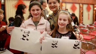 "Two girls show their paintings of panda with Chinese traditional painting artist Zhang Liping (C) during the event ""From China to Chicago: A Holiday Gathering & Celebration"" in Chicago, the United States, on Dec.14, 2019. (Xinhua/Wang Ping)"