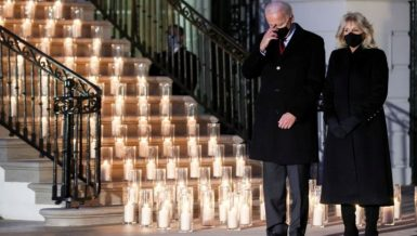 Candles were lit at the White House South Portico at sunset Monday, a day on which the number of Americans who died from COVID-19 broke the staggering record of 500,000.