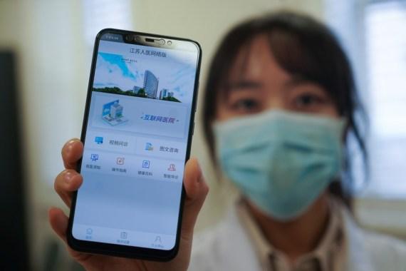 A staff member displays the mobile application of the Internet Hospital of Jiangsu Province Hospital in Nanjing, east China's Jiangsu Province, Feb. 7, 2020. (Xinhua/Ji Chunpeng)